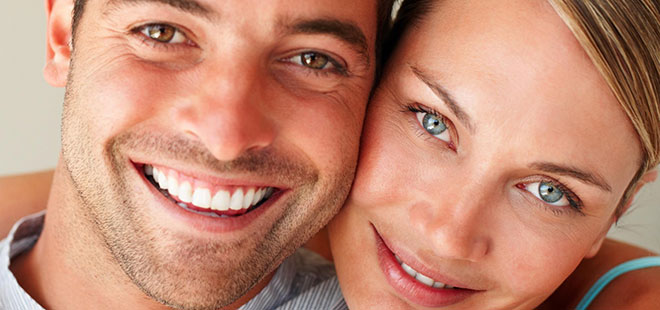 Couple smiling after Invisalign treatment from Scottsdale Cosmetic Dentist Dr. Lewandowski