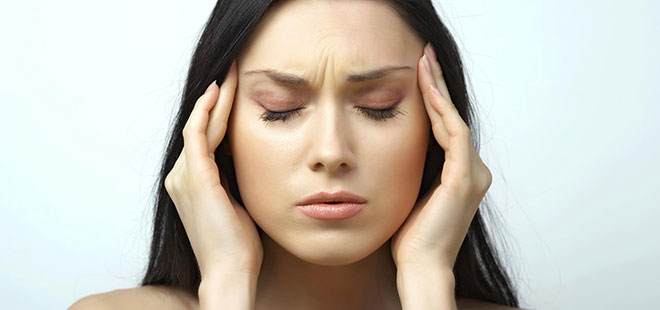 Woman holding her head because she needs TMJ Treatment
