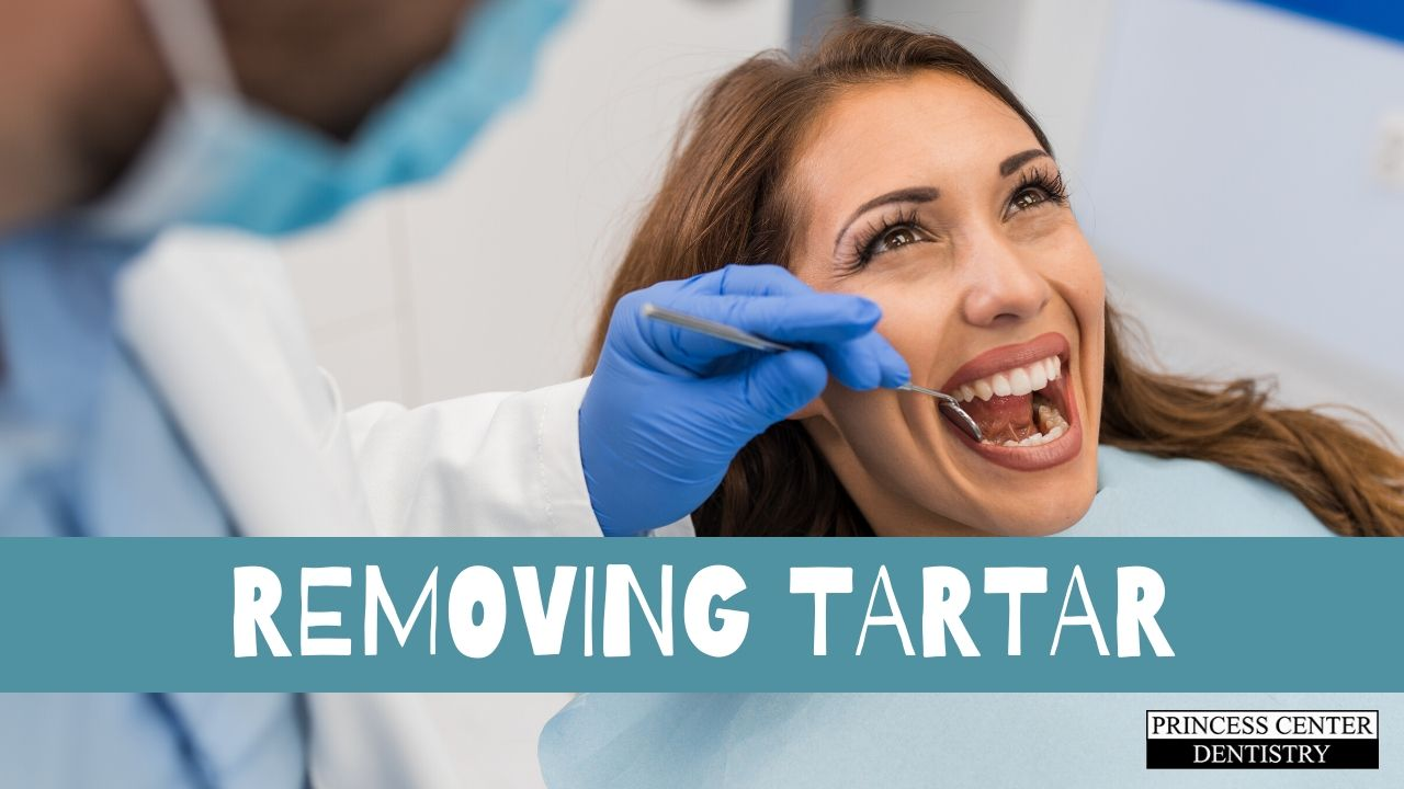 A hygienist removes tartar from a patient's teeth