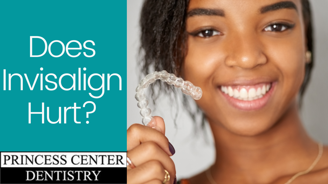 African American woman smiling and holding an Invisalign tray
